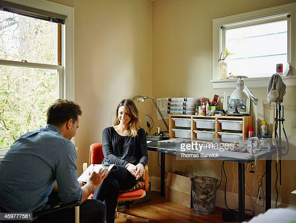 Couple in home office working on digital tablet