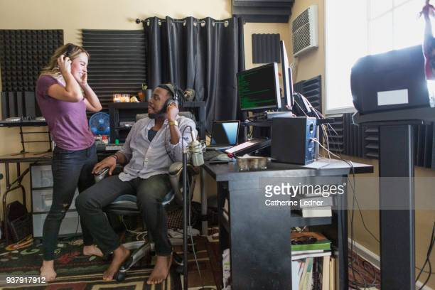 Couple in home sound studio with headphones listentening.