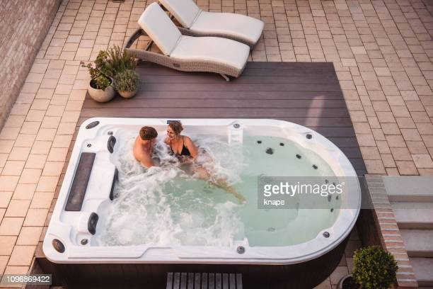 couple in hot tub pool spa whirlpool - hot tub stock pictures, royalty-free photos & images