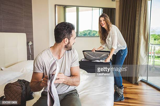 couple in hotel room getting dressed - packing stock pictures, royalty-free photos & images