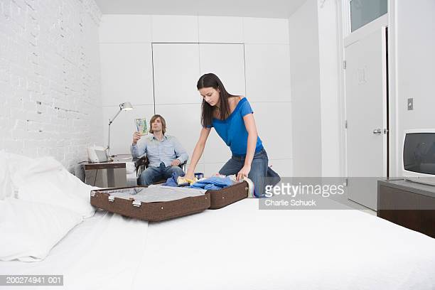 Couple in hotel room, woman on bed by suitcase, man looking at map