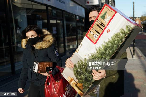 Couple in Hull city centre walk with a box containing a Christmas tree on November 13, 2020 in Hull, England. Hull recorded 726.8 new cases per...
