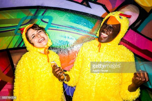 Couple in identical costumes listening to earbuds near graffiti wall