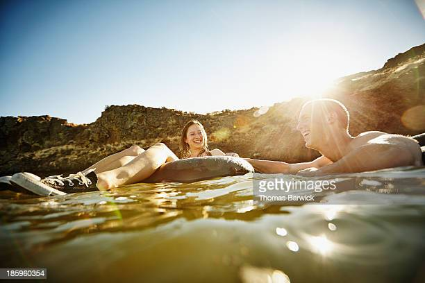 Couple in inner tubes laughing and smiling