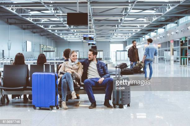 Couple in international airport waiting for flight