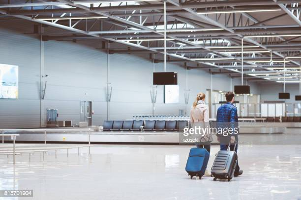 couple in international airport walking with luggage - luggage rack stock photos and pictures