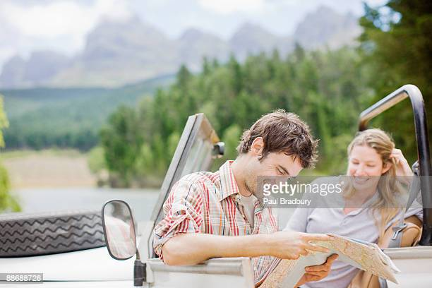 Couple in jeep looking at map