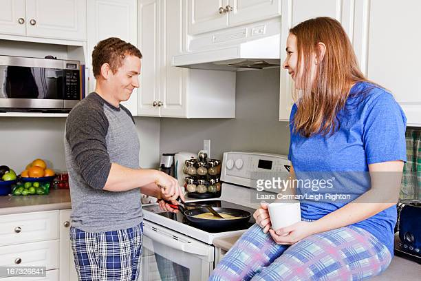 Couple in kitchen cooking breakfast.