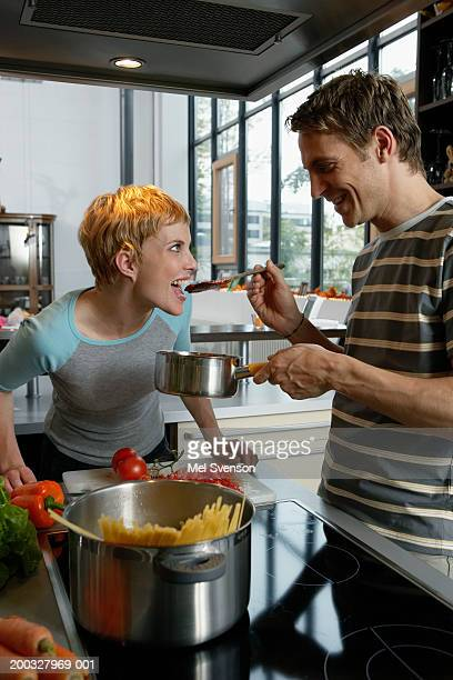Couple in kitchen cooking, man holding wooden spoon to woman's mouth