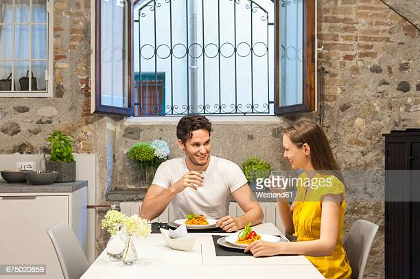 couple in kitchen eating pasta - mid adult stock pictures, royalty-free photos & images