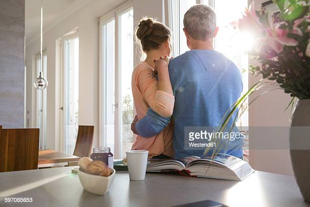 Couple in kitchen looking out of window, rear view