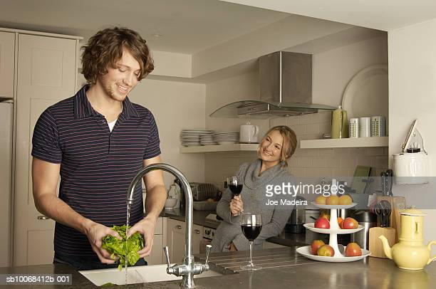 Couple in kitchen, man rinsing lettuce