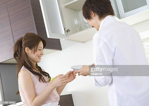 couple in kitchen - 手渡す ストックフォトと画像