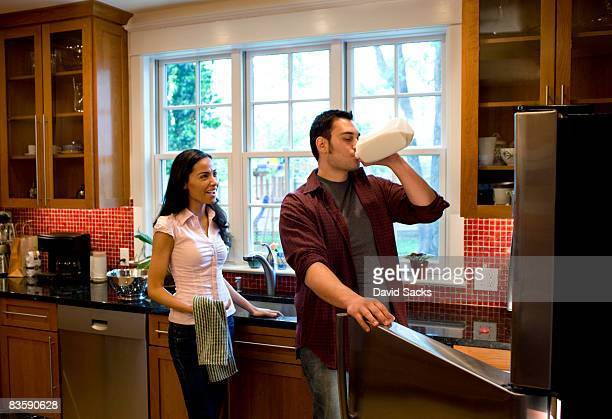 couple in kitchen - milk carton stock photos and pictures