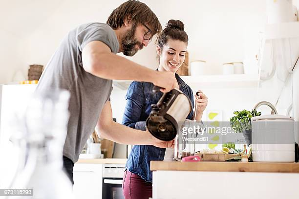 Couple in kitchen preparing coffee