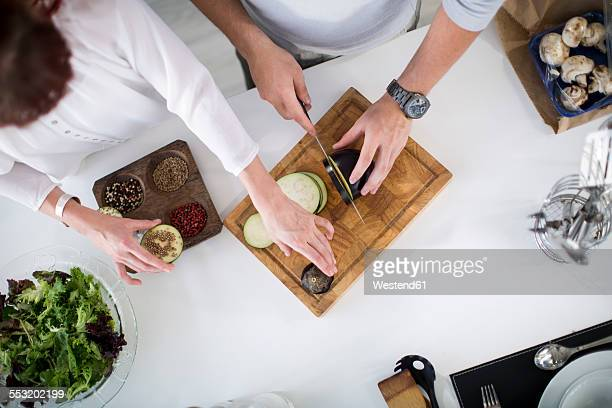 Couple in kitchen preparing eggplant