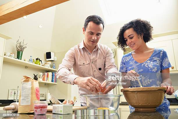 Couple in kitchen preparing eggs for baking