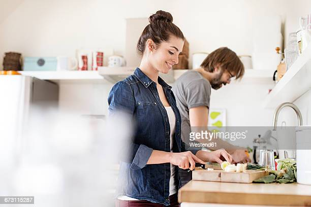 couple in kitchen preparing food - kochen stock-fotos und bilder