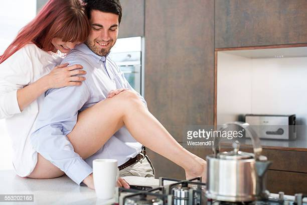 Couple in kitchen sharing an intimate moment