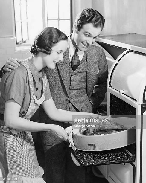 Couple in kitchen, wife taking roast from oven (B&W)