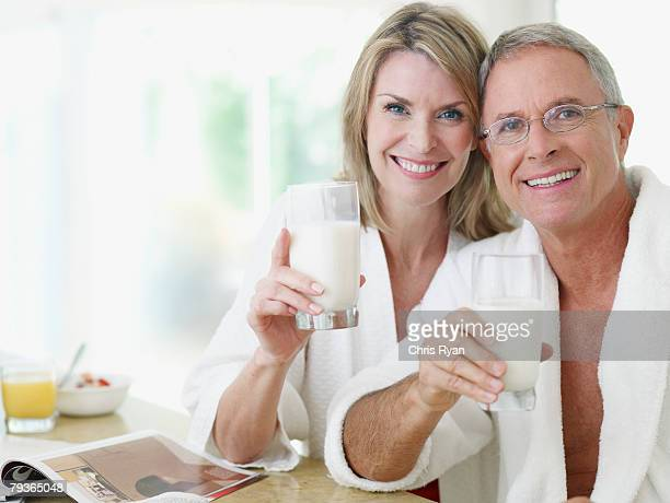 Couple in kitchen with glasses of milk and magazine