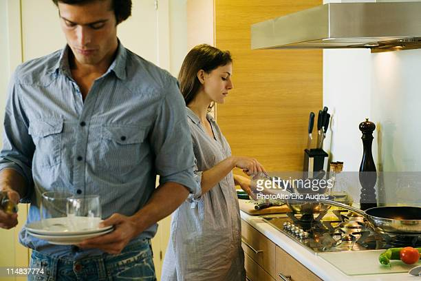 Couple in kitchen, woman cooking while man sets table