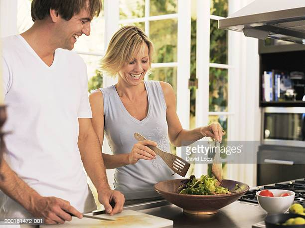 Couple in kitchen, woman tossing salad, smiling