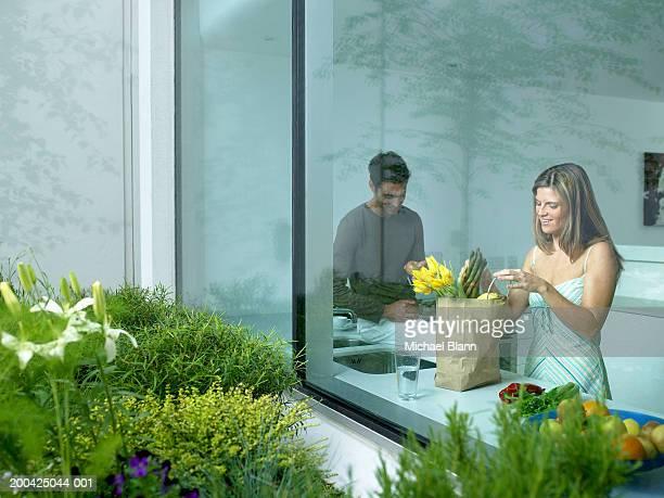 Couple in kitchen, woman unpacking shopping, view through window