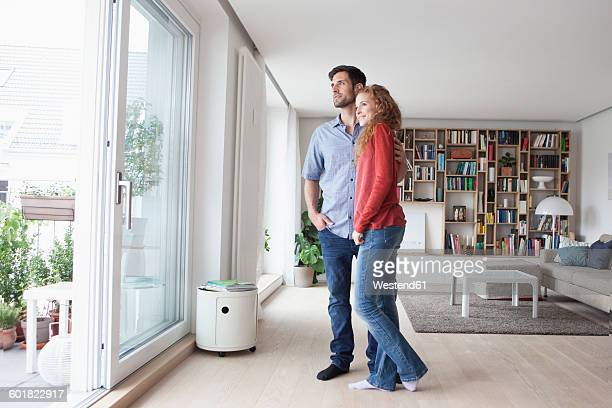 Couple in living room looking out of window