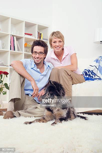 Young couple in living room with dog, smiling, portrait