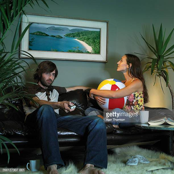 Couple in living room, woman staring at picture of tropical island