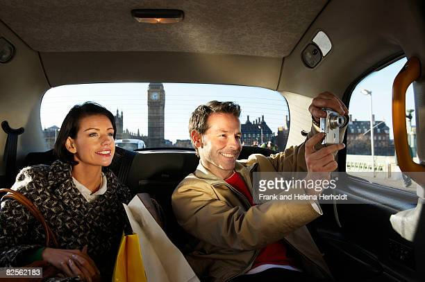 Couple in London taxi, Big Ben in view