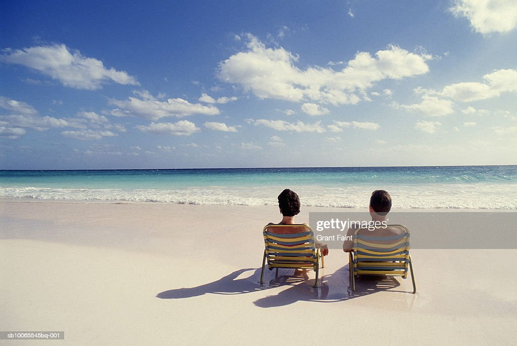 Couple in lounge chairs on beach, rear view : Stock Photo