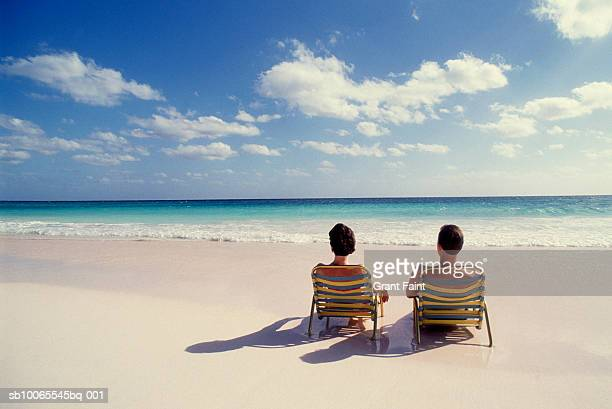 Couple in lounge chairs on beach, rear view