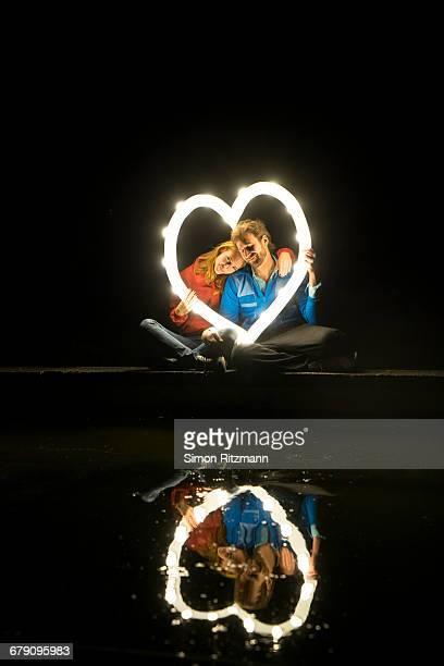 Couple in love holding illuminated heart at night