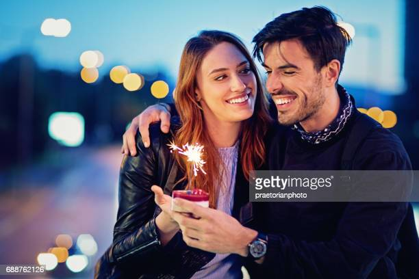 Couple in love is sitting on the bridge and celebrating