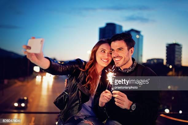 verliebte paar ist auf der brücke sitzen und nehmen ein selbstporträt - erotikbilder stock-fotos und bilder