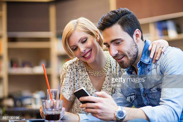 Couple in love looking at photos on a smart phone