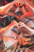 closeup couple hands making heart shape