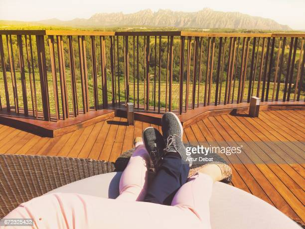 Couple in love relaxing laying in big couch on the terrace outdoor with good weather in springtime contemplating the landscape view with Montserrat mountain range in the background during weekend activities in the Catalonia region.