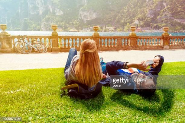 couple in love relaxing on the grass, shores of lake como italy - trento foto e immagini stock