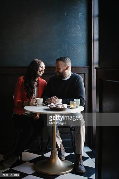 a couple in love, sitting close together. - side by side stock pictures, royalty-free photos & images