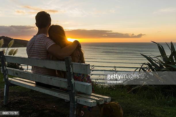 couple in love sitting on bench looking at sunset - romantic sunset stock pictures, royalty-free photos & images