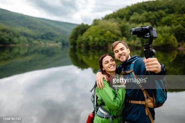 彼らは永遠にこの瞬間を思い出すことができるように自分撮りを取る愛のカップル - モバイル撮影 ストックフォトと画像
