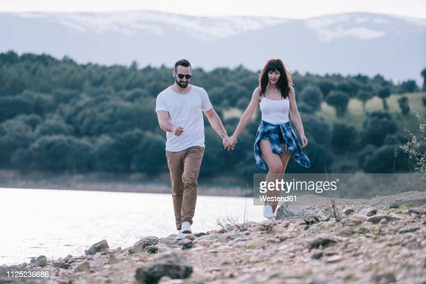 couple in love walking hand in hand in nature - heterosexuelles paar stock-fotos und bilder