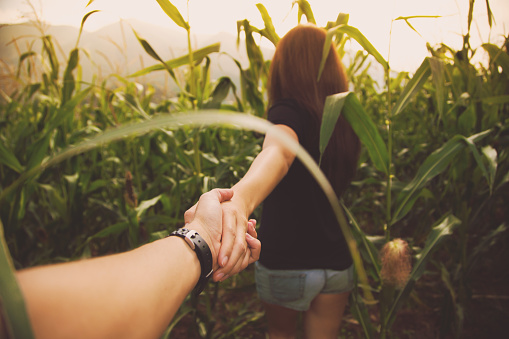 Couple in love walking on summer inside a corn field with the girl leading the way inside the maze holding hands and the picture is taken from the personal perspective of boyfriend during beautiful sunset in the Catalan Pyrenees. Follow me. - gettyimageskorea
