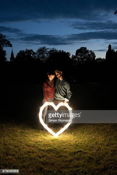 Couple in love with illuminated heart outdoors