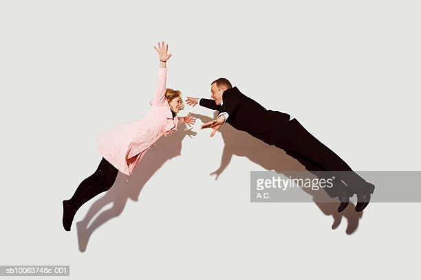 Couple in mid air against white background, side view