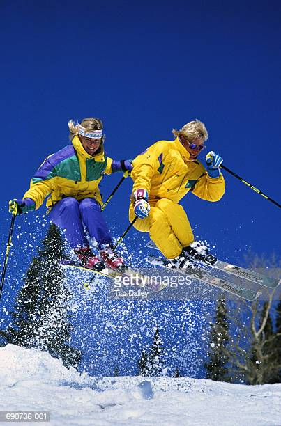 couple in mid-air leap,man in yellow ski suit - ski pants stock pictures, royalty-free photos & images