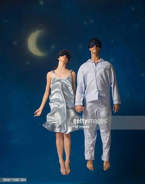 couple in mid-air wearing sleep mask - women in slips stock pictures, royalty-free photos & images